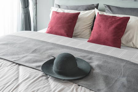 red pillows: black hat on bed in modern bedroom design with red pillows Stock Photo
