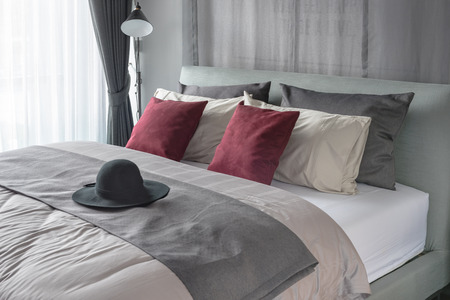 red pillows: red pillows and black hat on bed in modern bedroom design Stock Photo