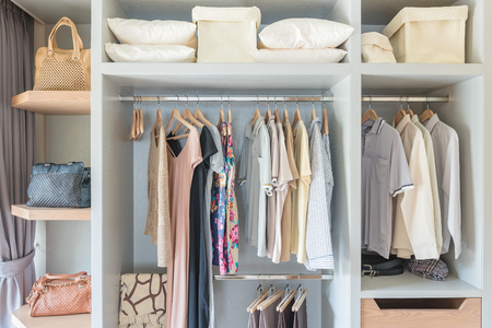 clothes hanging on rail in wooden closet at home