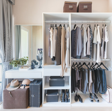 walk in closet: white wardobe and dressing table with clothes hanging in walk in closet