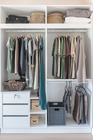 clothes and dress hanging on rail in white closet at home