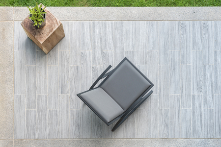 home furniture: modern grey leather chair with vase of plant on terrace, top view