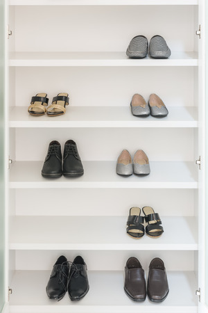shelve: white wardrobe with male and female shoes on shelve Stock Photo