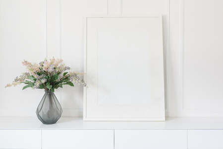 glass vase of flower with white picture frame on white table