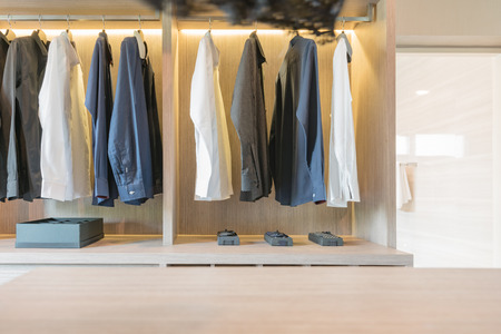 walk in closet: clothes hanging in wooden walk in closet, modern style