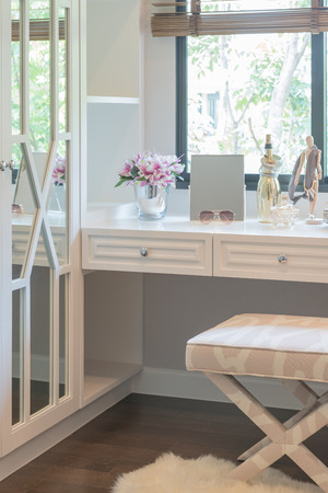 white dressing table and chair with women's accesories