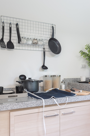 stainless steel range: iron frying pan and utensils hanging on the wall in kitchen room