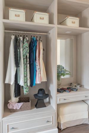 walk in closet: modern wooden wardrobe with clothes hanging on rail in walk in closet design interior