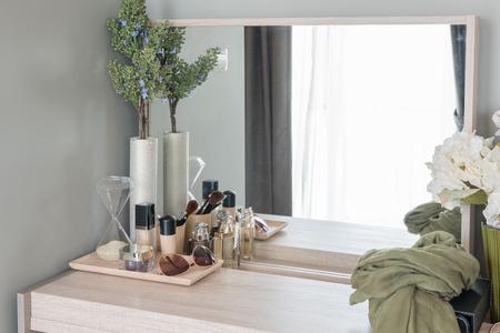 vistiendose: Concepto de belleza y maquillaje: espejo de mesa, flores, perfume, joyería y pinceles de maquillaje en la mesa de madera, close-up