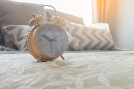 modern alarm clock on bed in bedroom, interior design