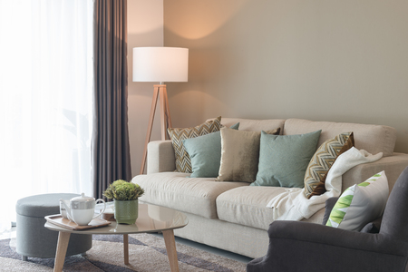 modern living room with green pillows on cozy sofa and wooden lamp, interior design Archivio Fotografico