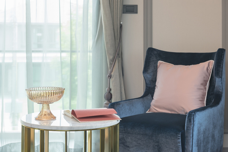luxury living room: blue sofa with pink pillow and round table in living room, interior design Stock Photo