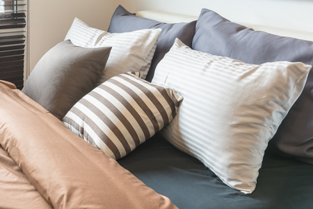 hotel bedroom: set of pillows on modern bed in modern bedroom style Stock Photo