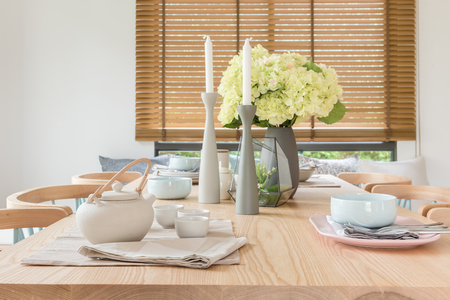 house ware: wooden dining table in modern dining room with table set and vase of plants, interior design concept