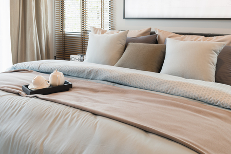 suite: king bed size with set of pillws and set of tea on tray in classic bedroom style, interior design concept