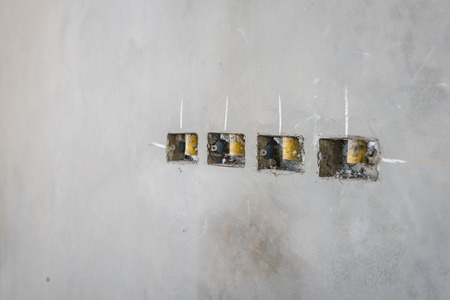 electrical socket hole on precat concret wall, outlet electric wires in constuction site Stock Photo