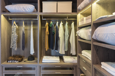 wooden wardrobe in walk in closet with clothes hanging on rail, interior design concept Фото со стока