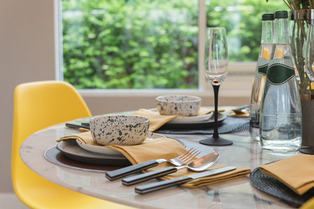 table set on round table with yellow chair in modern style dining room, interior design concept Stock Photo