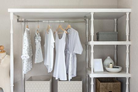 Camisas de color blanco colgadas en el riel en un armario de madera de estilo clásico, concepto de diseño de interiores