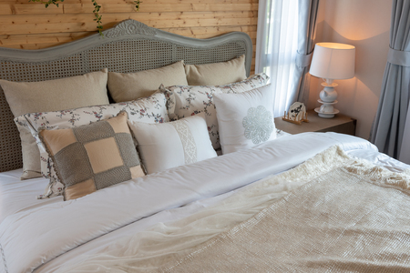 classic bedroom style with set of pillows on bed and classic lamp in white color tone, interior design decoration concept 写真素材