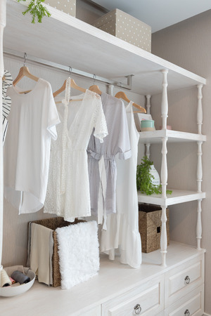 classic closet style with clothes hanging, white color tone wardrobe with clothes, interior decoration design concept Stock Photo
