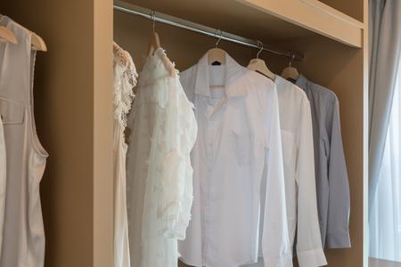 nowoczesna szafa z ubraniami wiszącymi na szynie, biała drewniana szafa, koncepcja aranżacji wnętrz