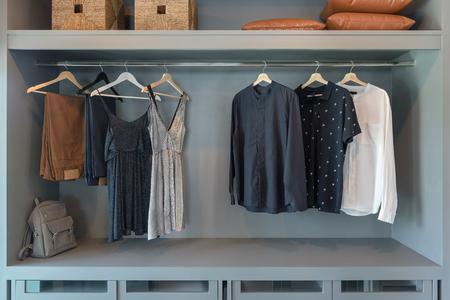 Armario moderno con ropa colgada en el riel, armario de madera blanca, concepto de diseño de interiores Foto de archivo