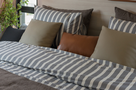 modern bedroom with set of pillows and stripe pattern blanket on bed, interior design decoration concept 免版税图像