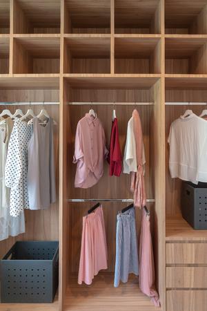 armadio moderno con vestiti appesi su rotaia, armadio in legno bianco, concetto di interior design