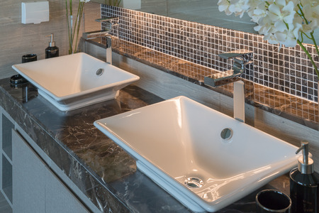 Bathroom interior in new luxury home, sink with faucet and decoration set, white washbasin and faucet