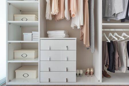 armario moderno con un conjunto de ropa colgada en el riel, concepto de diseño de interiores de armario moderno