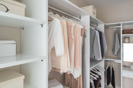 modern wardorbe with set of clothes hanging on rail, modern closet interior design concept Stock Photo