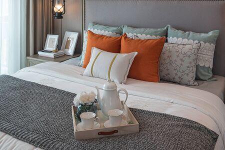 klassischer Schlafzimmerstil mit Kissen auf dem Bett mit Tablett mit Teetasse, Innenarchitekturkonzept