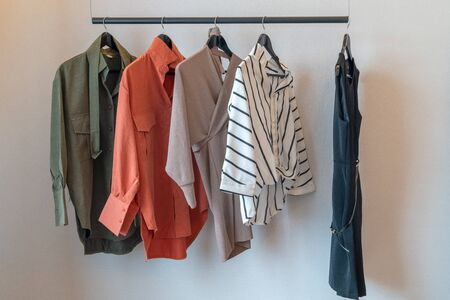 armadio moderno con set di vestiti appesi su binario, concetto di interior design moderno dell'armadio