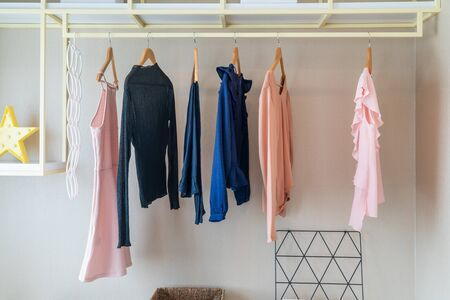modern wardrobe with set of clothes hanging on rail, modern closet interior design concept Stockfoto