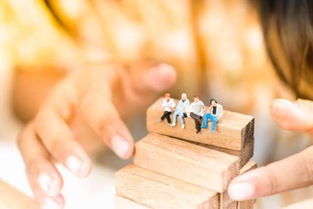 Miniature people: Small businessmen sitting on wooden blocks. Education, Money, Financial and Business Growth concept.