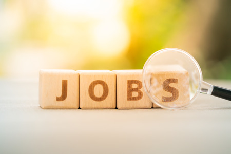 Wood block word JOB and magnifying glass with copy space using as background Choice of the best suited employee, HR, HRM, HRD, job recruiter concepts.