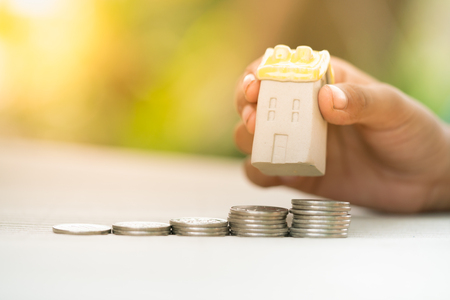 Concept for property ladder, mortgage and real estate investment. Woman's hand putting house model on top of coins stack. Stock Photo