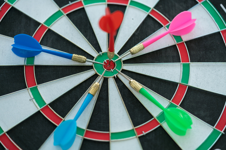 Red dart arrow hitting in the target center of dartboard with other dart arrows background. Target business, achieve and victory concept.