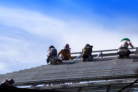 skilled labour: Actual construction workers working together to install a steel roof frame. Stock Photo