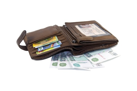 the opened leather wallet of brown color with credit cards, documents and banknotes on a white background photo