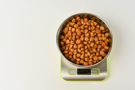 Dry pet food in a metal bowl on a green electronic scale