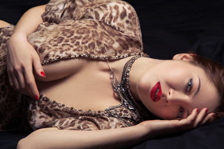 female sexuality: Glamor portrait of beautiful woman lying on black bed