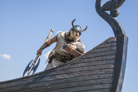 viking ship: Strong Viking on his ship looking to beach Stock Photo