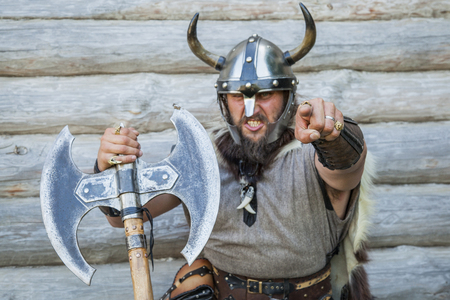 Portrait of the angry viking looking and pointing at camera.