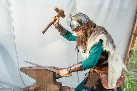 blue helmet: Strong viking is repairing his sword Stock Photo