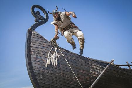 Strong Viking jumping from his ship to attack Stockfoto