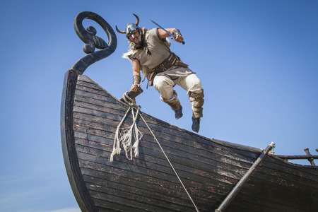 viking helmet: Strong Viking jumping from his ship to attack Stock Photo