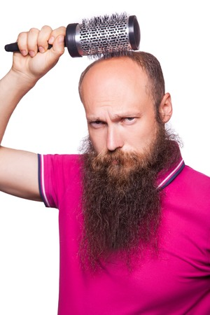 hairline: Human alopecia or hair loss - adult man hand holding comb on bald head.