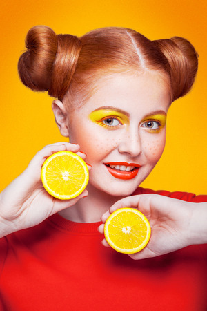 Young beautiful funny fashion model with lemon slice on orange background. with makeup and hairstyle and freckles. studio shot, looking at camera with smile. Stock Photo
